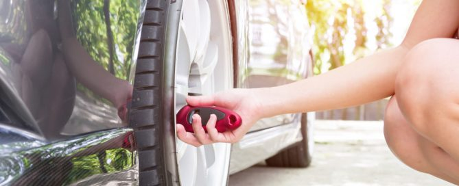 women checking tire pressure